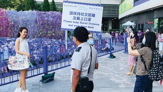 A woman posed for photos in front of a flower garden in North Point while a security guard held a banner warning people to take anti-virus measures.