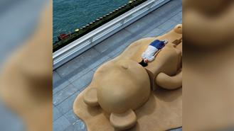 A visitor enjoys the sunshine on a BE@RBRICK figure at the Ocean Terminal Deck, a tourist attraction which has been