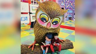 A boy reads a book close to the large figure of an owl and another boy at a shopping mall in Causeway Bay.