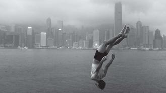 A man plunges into the Victoria Harbour in Tsim Sha Tsui. His streamlined figure stands out against the steady water surface and the backdrop of city skyscrapers.