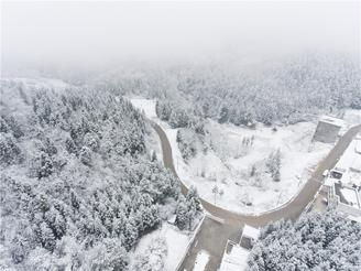 Heavy snowfall envelops a stretch of forestland and nearby village houses in white in Bijie city, Southwest China's Guizhou province.