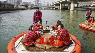 A 40-minute river tour took tourists in Japan around Osaka's Nakanoshima Park while they had grilled mochi.