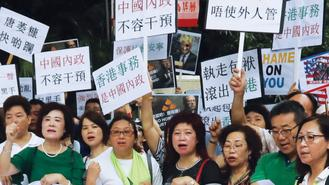 Members of the Social Affairs Committee of the Hong Kong Federation of Trade Unions display placards on Monday outside the US Consulate General in Hong Kong and Macao.
