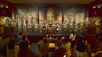 Visitors take photos of Buddhist statues at the Tokyo National Museum Heiseikan in Taito Ward, Tokyo
