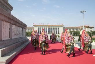 People from all walks of life in China attended a ceremony to present flower baskets to deceased national heroes at Tian'anmen Square on Wednesday morning.