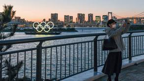 A person takes a photo of floating Olympic rings