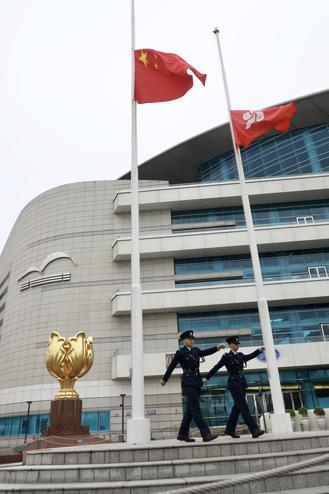 The Chinese national flag and Hong Kong regional flag fly at half-mast at Golden Bauhinia Square to mourn coronavirus victims on Saturday.