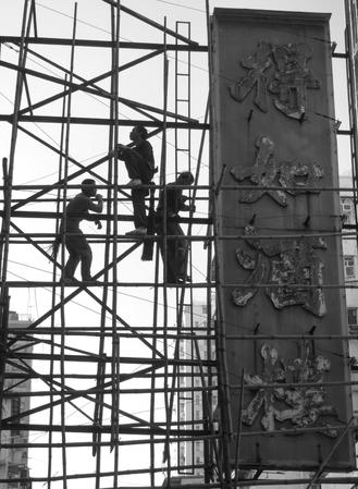 Construction workers balance themselves on bamboo scaffolding erected for renovating one of the oldest teahouses in Yau Ma Tei.
