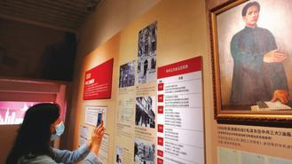 A woman took pictures of an exhibition celebrating the 100th anniversary of the Communist Party of China during a visit to the Guangzhou Museum.