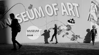 Shadows of visitors walking past the Hong Kong Museum of Art advertising billboards in Tsim Sha Tsui become incorporated in the murals.