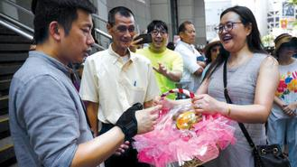 Members of the public present a fruit basket to a police representative in appreciation of the force's dedication and efforts in keeping public order and safety during the recent wave of protests in Hong Kong.