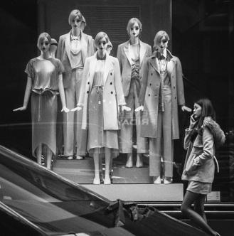 A woman kitted out for a wintry day passes five mannequins displaying items for a spring wardrobe.