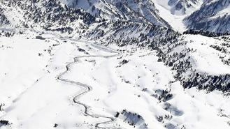 A meandering road appears on a mountain in Japan as snow removal progresses, ahead of the spring tourist season.