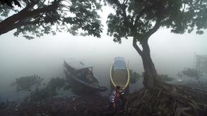 A woman walks on the banks of a river through thick haze from forest fires in Palembang, South Sumatra, Indonesia