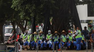 Cleaners take a break under a big tree in Central. The lush and extensive shrub provides a shelter for the outdoor workers to chill out in the stiflingly hot summer.