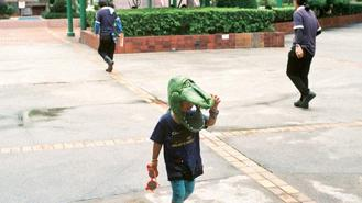 This youngster takes things in his stride as he strolls in a Kowloon Bay community wearing a crocodile-head mask.