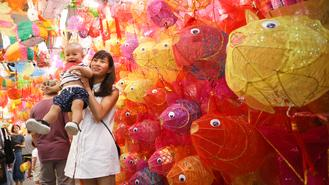 A mother with her child poses for a photograph in front of a wall of lanterns at the Yuen Long Tai Kiu Market on Tuesday. The Mid-Autumn Festival falls on Friday this year when people celebrate the occasion by lighting lanterns, eating mooncakes, and watching fire dragon dances in the city.