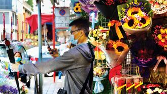 A customer wearing a surgical mask snaps a photo of a rose in his hand at a Hong Kong flower market on Thursday, a day before Valentine's Day.
