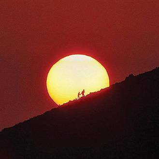 A pair of backpackers climb up a mountain in  Brick Hill on Hong Kong Island near Wong Chuk Hang. The sun glows and their silhouettes form a beautiful image.