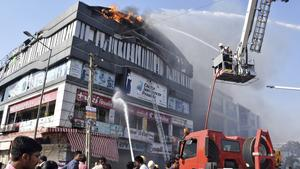 Firefighters work to douse flames on a building in Surat, in the western Indian state of Gujarat