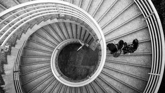 A bird's-eye view of a couple ascending the spiral outdoor stairs near the iconic Bank of China Tower in Central.