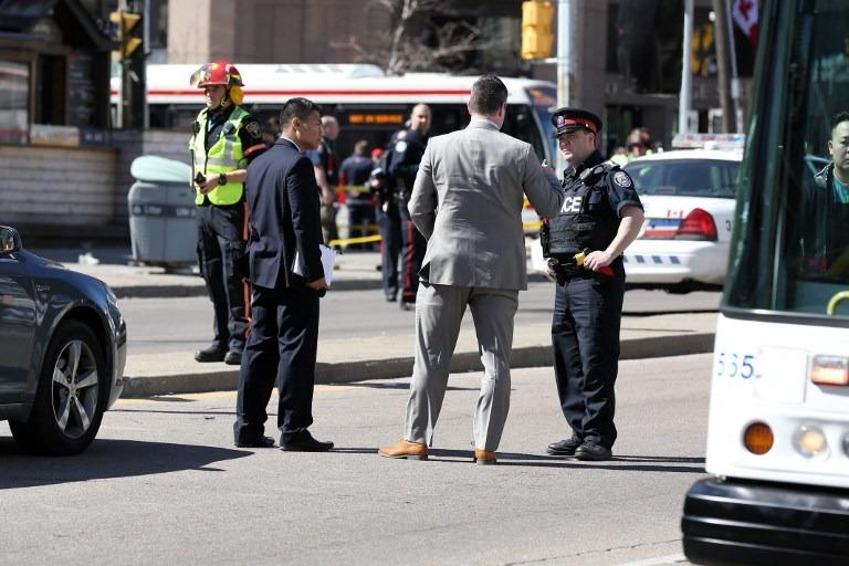 67f16fa1f1 Police officers stand near the crime scene after a truck hit several  pedestrians in Toronto