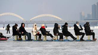Tourists play on the frozen Songhua River in Harbin, the capital of northeast China's Heilongjiang province on Jan 15, 2018.
