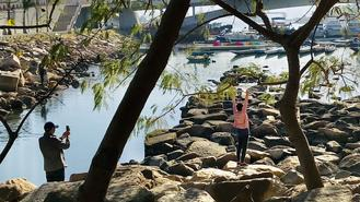 A woman basks in the sunshine while being photographed near the water in Tseung Kwan O.