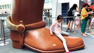 A girl enjoys her playtime straddling across a larger-than-life boot installation at the Toy Story Exhibition in Tsim Sha Tsui.