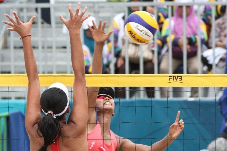 Indonesia's Yokebed Purari Eka (back) hits the ball as China's Wang Fan  (front) tries to block during their women's quarterfinal beach volleyball  match ...