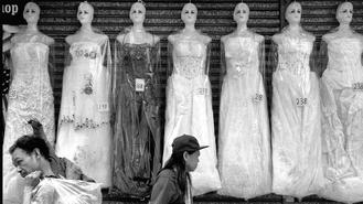 People walk past a row of gown-clad mannequins displayed in a shop in Sham Shui Po.