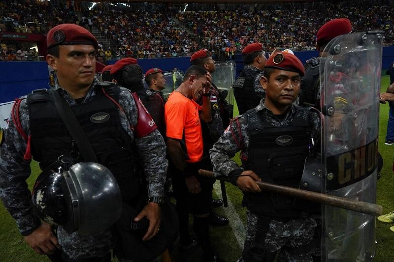 c13316e07 Police protect referee Moacir Eriberto Guedes during the Peladao final  amateur soccer tournament at Arena da Amazonia in Manaus