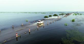 The road is submerged under water because of the rising water level of China's largest freshwater lake Poyang Lake.