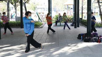 Residents wearing face masks play tai chi sword, at Lingnan Garden, Mei Foo, a large private housing estate in Lai Chi Kok, Kowloon.