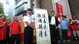 HKFTU representatives present a piece of calligraphy to an officer at the police headquarters Tuesday, praising the police for cracking down on the use of violence by protesters.