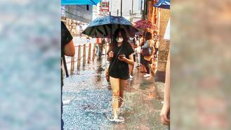 A girl with an umbrella was pictured walking along a flooded sidewalk during a sudden downpour in Causeway Bay.