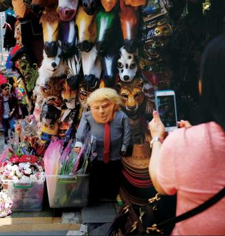 A woman snaps a photo of a Donald Trump mask, mounted on an appropriately dressed dummy, in Central.