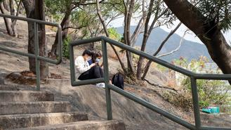 Young people wearing masks take a rest at Garden Hill, an ideal place to enjoy a view of the city in the Sham Shui Po district in Kowloon.