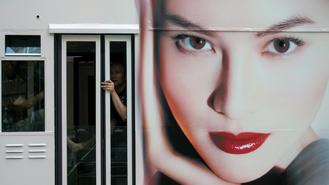 A passenger on a tram looks out of a window, next to a large advertisement featuring a model, who appears to gaze into a street in Central.