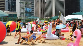 Beachgoers seize a chance to sunbathe amid Hong Kong's towers of finance on an artificial sand beach set up at the Central Harbourfront.