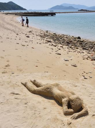 A lifelike sand sculpture lies on the beach on Sharp Island, leaving passersby wondering if it's a man covered with sand or just a human figure made of sand.