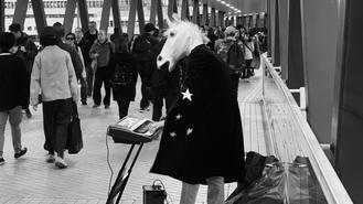 A busker wearing a horse head mask and a cape with stars plays electronic keyboard on a footbridge in Central, but he doesn't seem to have drawn much attention from the crowds passing by.