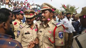 People throw flower petals on Indian policemen guarding the area where rape accused were shot