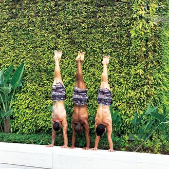 Three men practice yoga at the reopned Avenue of Stars in Tsim Sha Tsui. Their standing-upside-down posture, skin and muscular tones and tattoos create an eye-catching harmony with the lush green backdrop.