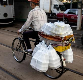 A common lunch-time sight in Hong Kong — a delivery man pedals his way through a street in Central on a bicyle almost filled to the hilt with bags of lunch boxes.