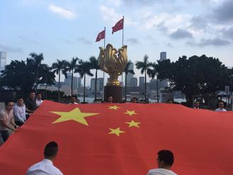 More than 100 young people gathered at Golden Bauhinia Square on Tuesday to sing the national anthem in a show of  patriotism for the country.