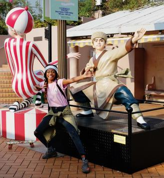 A visitor to Kowloon Park strikes a matching pose in front of a character on the Avenue of Comic Stars.