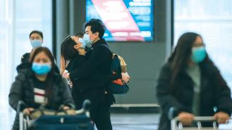 Two young people, both wearing surgical masks, kiss at Hong Kong International Airport.