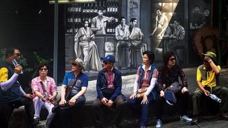 Sightseers taking a breather form a colorful foreground for a historic black and white mural in SoHo, Central.