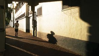 The silhouette of a man walking along a street in Sham Shui Po appeared on the wall as the fading sun's rays cast shadows on him.